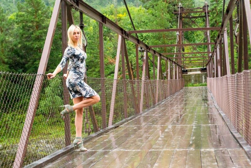 La ragazza bionda sta su un ponte costruito con metallo e legno fotografie stock