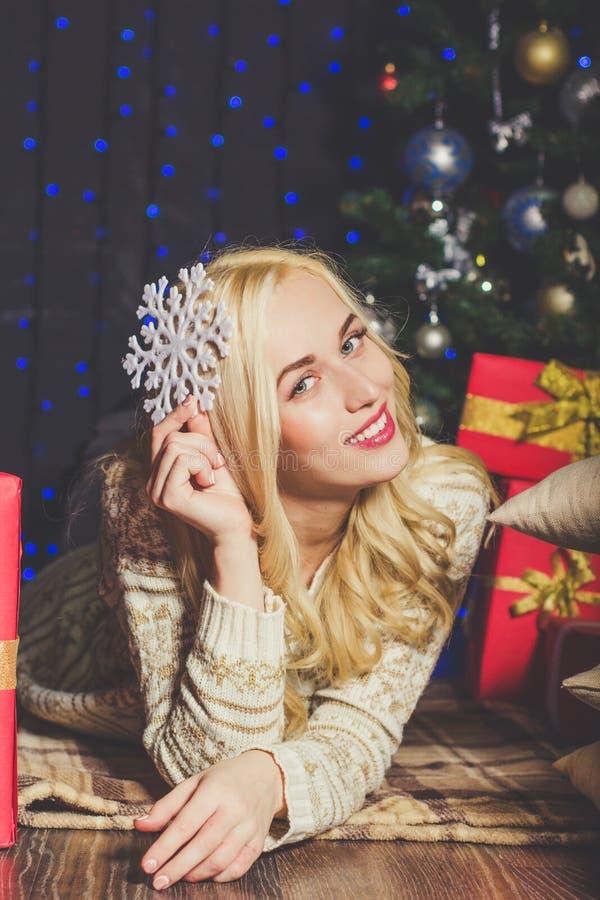 La ragazza bionda sta tenendo il fiocco di neve bianco, natale immagini stock libere da diritti
