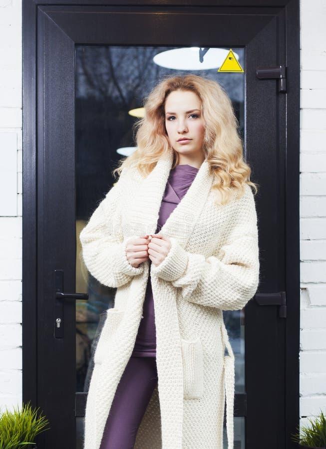 La ragazza bionda stupefacente che posa in un bianco ha tricottato il cappotto sulla via Modo bellezza immagine stock