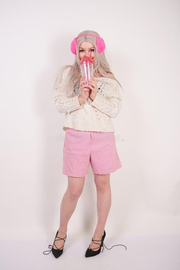 La ragazza bionda sveglia sta in vestiti luminosi casuali alla moda e beve l'acqua da una tazza di vetro trasparente rosa con gli immagini stock