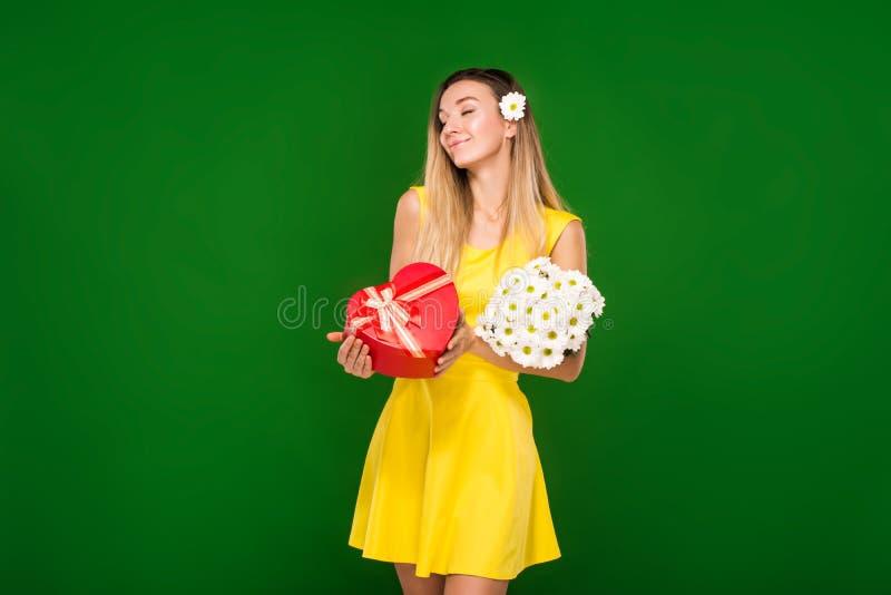La ragazza bionda in un vestito giallo tiene un mazzo dei camomiles e di un contenitore di regalo fotografia stock