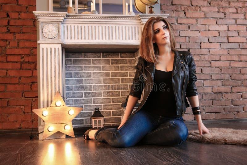 La ragazza in bomber neri che posano seduta sul pavimento fotografie stock