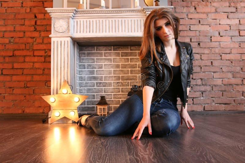 La ragazza in bomber neri che posano seduta sul pavimento immagini stock