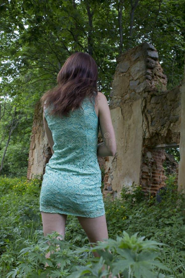La ragazza in breve vestito sta indietro su fondo delle rovine fotografia stock libera da diritti