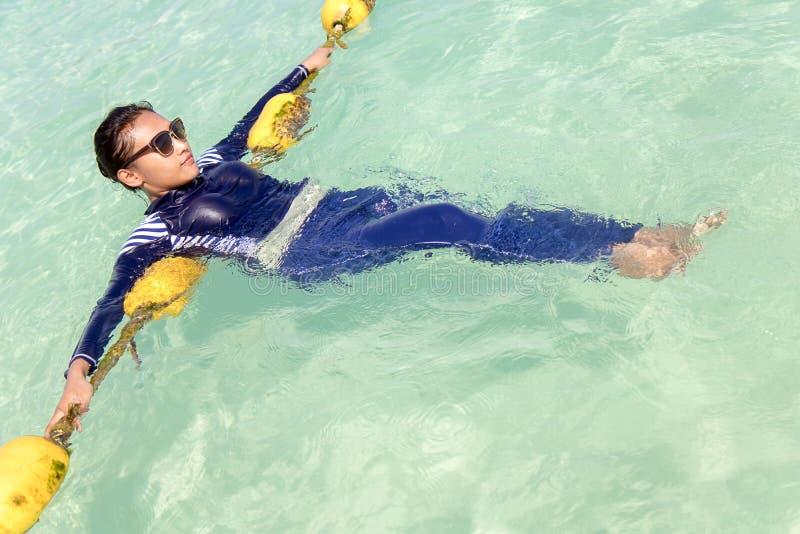 La ragazza in burkini blu si rilassa in un mare del turchese immagine stock libera da diritti
