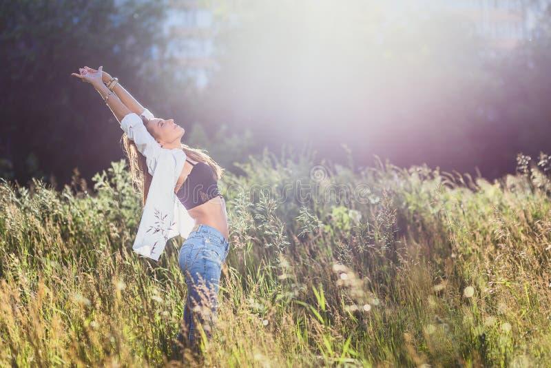 La ragazza in camicia bianca ha sollevato le sue mani su di estate immagine stock libera da diritti