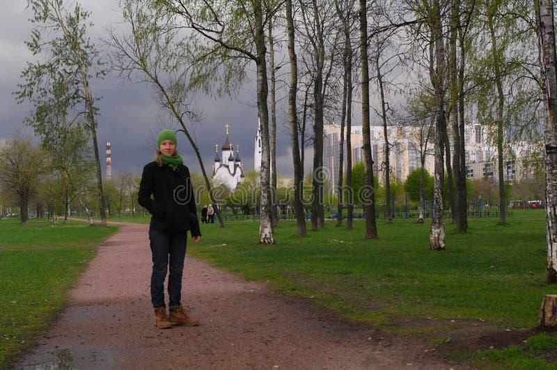 La ragazza cammina lungo il percorso in parco con un chuch nel fondo immagine stock