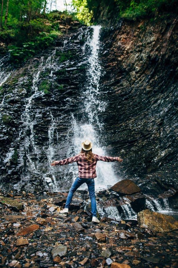 La ragazza in cappello sta su roccia e gode della cascata immagine stock libera da diritti