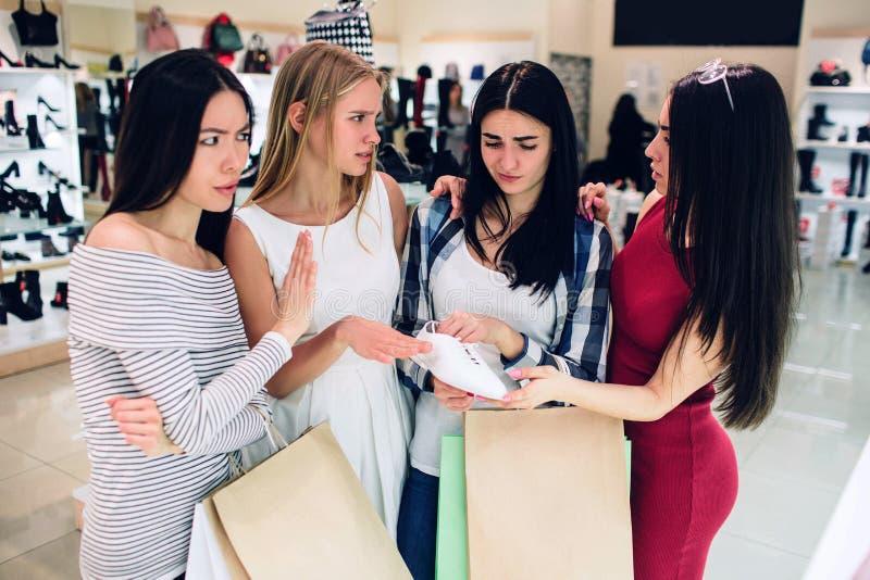 La ragazza castana in camicia sta tenendo uno degli incroci bianchi Dubita per comprarla Il suo amico sta dando consiglia a lei fotografie stock libere da diritti