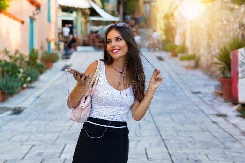 La ragazza castana della città dell'estate cammina giù la via ed ascolta musica immagini stock libere da diritti