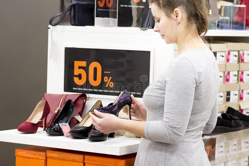La ragazza castana in deposito sta scegliendo le scarpe la donna nel boutique di modo compra le scarpe Comperando nel centro comm immagini stock libere da diritti