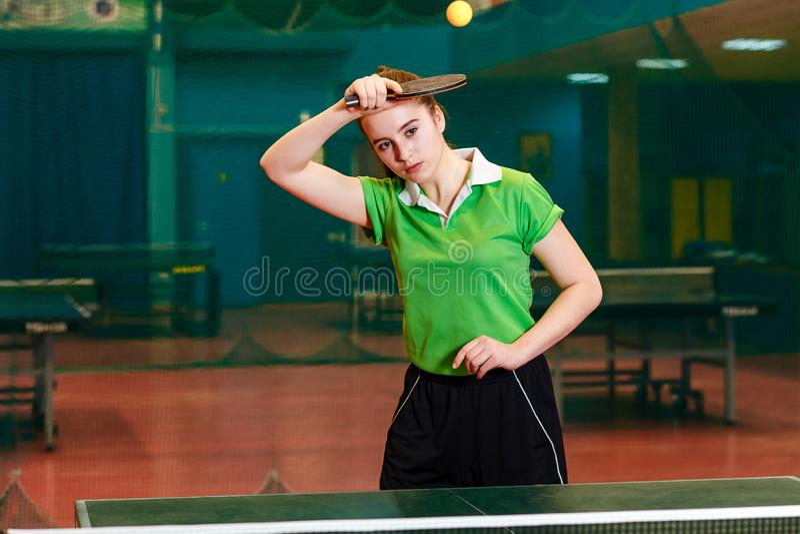 La ragazza castana di quindici anni caucasica batte il ping-pong della palla in una palestra specializzata Destra del rotolo nel  fotografie stock
