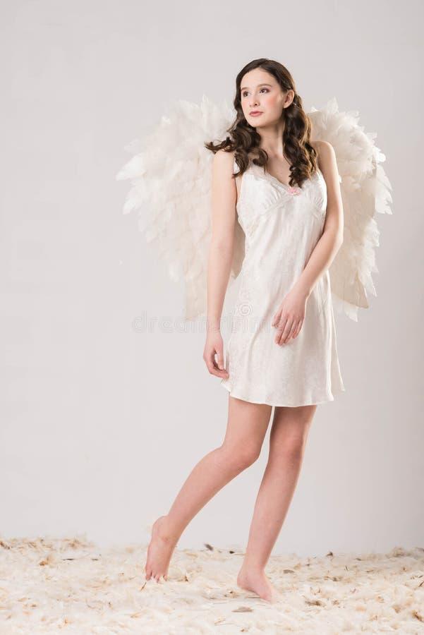 La ragazza castana nel bianco con le ali di angelo sta fotografie stock libere da diritti