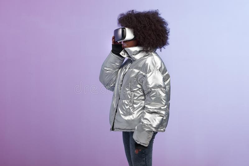 La ragazza castana riccia d'avanguardia vestita di un in un rivestimento colorato d'argento utilizza i vetri di realtà virtuale n immagine stock