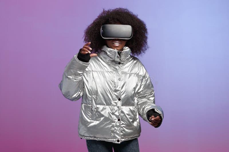 La ragazza castana riccia d'avanguardia vestita di un in un rivestimento colorato d'argento utilizza i vetri di realt? virtuale n fotografie stock libere da diritti