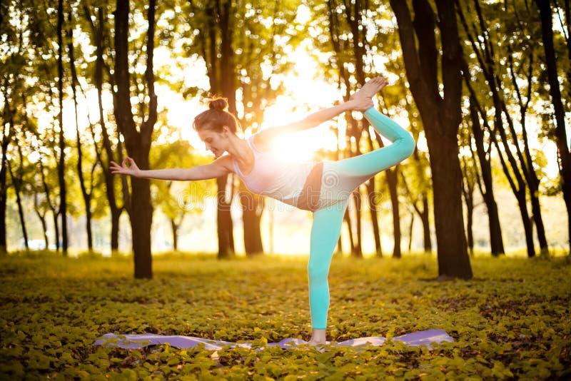 La ragazza castana sottile gioca gli sport ed esegue le pose di yoga nel parco di autunno su un fondo del tramonto Donna che fa g fotografia stock