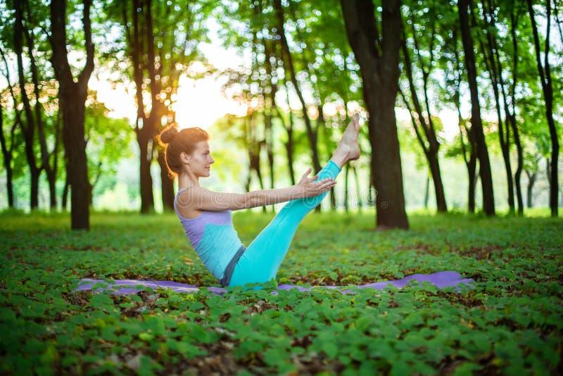 La ragazza castana sottile gioca gli sport ed esegue le pose di yoga in un parco dell'estate su un fondo del tramonto Donna che f fotografia stock libera da diritti