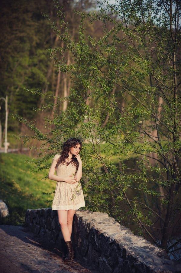 La ragazza castana sta sul ponte vicino all'acqua fotografie stock