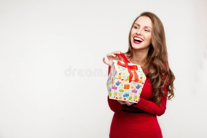 La ragazza castana sta tenendo un presente e una risata per il giorno del ` s del biglietto di S. Valentino Su fondo bianco immagini stock libere da diritti