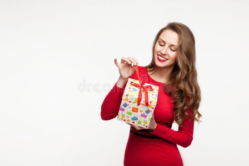 La ragazza castana sta tenendo un presente e una risata per il giorno del ` s del biglietto di S. Valentino Su fondo bianco immagine stock libera da diritti