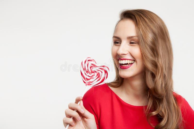 La ragazza castana sta tenendo una lecca-lecca come un cuore e una risata per il giorno del ` s del biglietto di S. Valentino fotografia stock