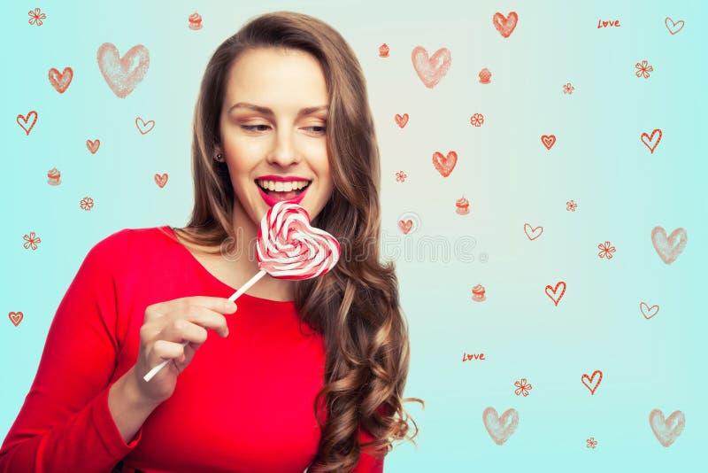 La ragazza castana sta tenendo una lecca-lecca come un cuore e una risata per il giorno del ` s del biglietto di S. Valentino fotografie stock libere da diritti