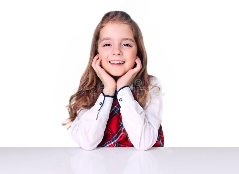 La ragazza caucasica del bambino alla tavola vuota ha isolato il fondo immagini stock