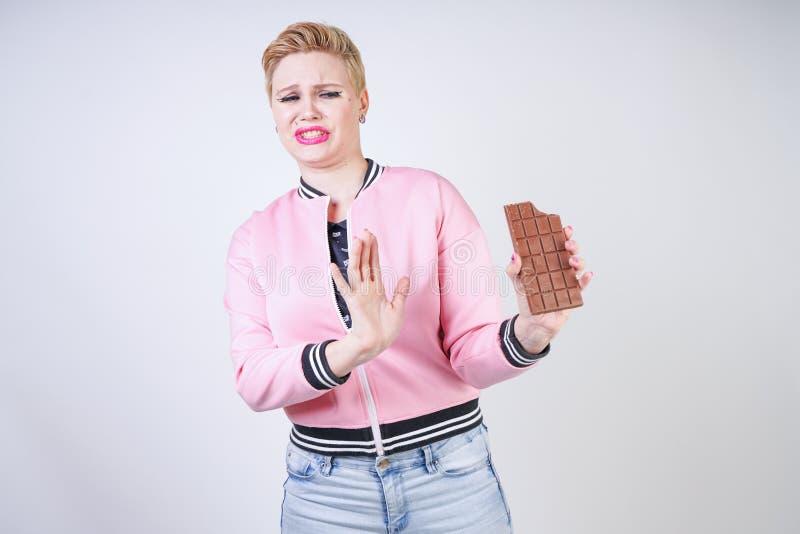 La ragazza caucasica di dimensione più con i brevi supporti di taglio di capelli in rivestimento di sport rosa con la barra di ci fotografia stock libera da diritti