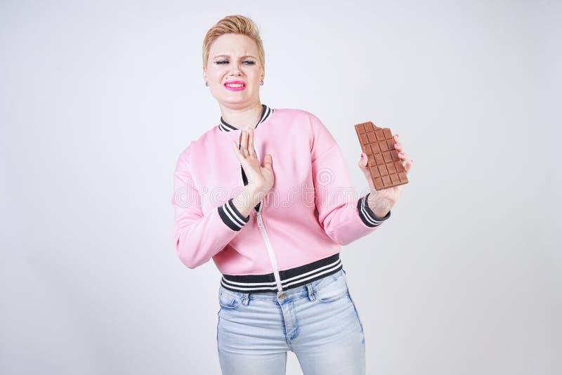 La ragazza caucasica di dimensione più con i brevi supporti di taglio di capelli in rivestimento di sport rosa con la barra di ci immagini stock libere da diritti