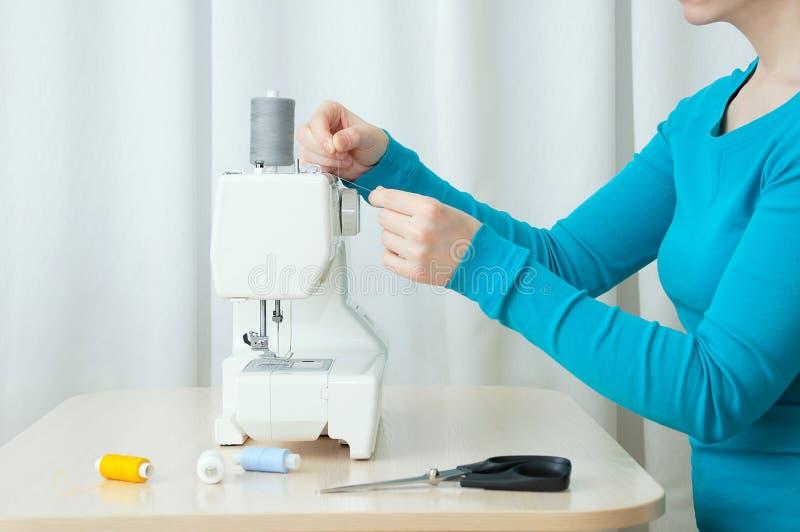 La ragazza caucasica esegue il filo sulla macchina per cucire Primo piano immagine stock