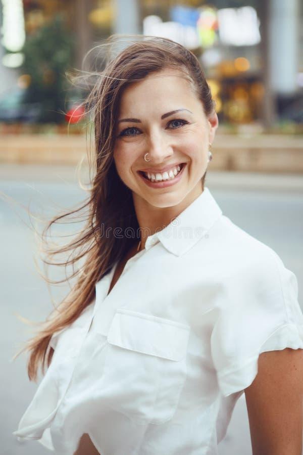La ragazza caucasica sorridente della donna con gli occhi azzurri con capelli lunghi biondi sudici il giorno ventoso all'aperto,  immagine stock