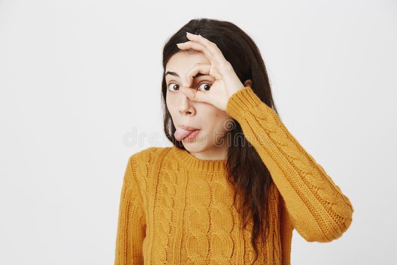 La ragazza caucasica sveglia divertente che attacca fuori la lingua e che mostra okay cede firmando un documento l'occhio mentre  immagine stock libera da diritti