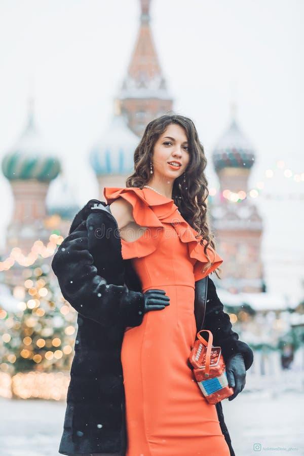 La ragazza caucasica in un vestito rosso tiene a disposizione una fisarmonica nei precedenti dell'inverno della cattedrale del ba fotografia stock libera da diritti