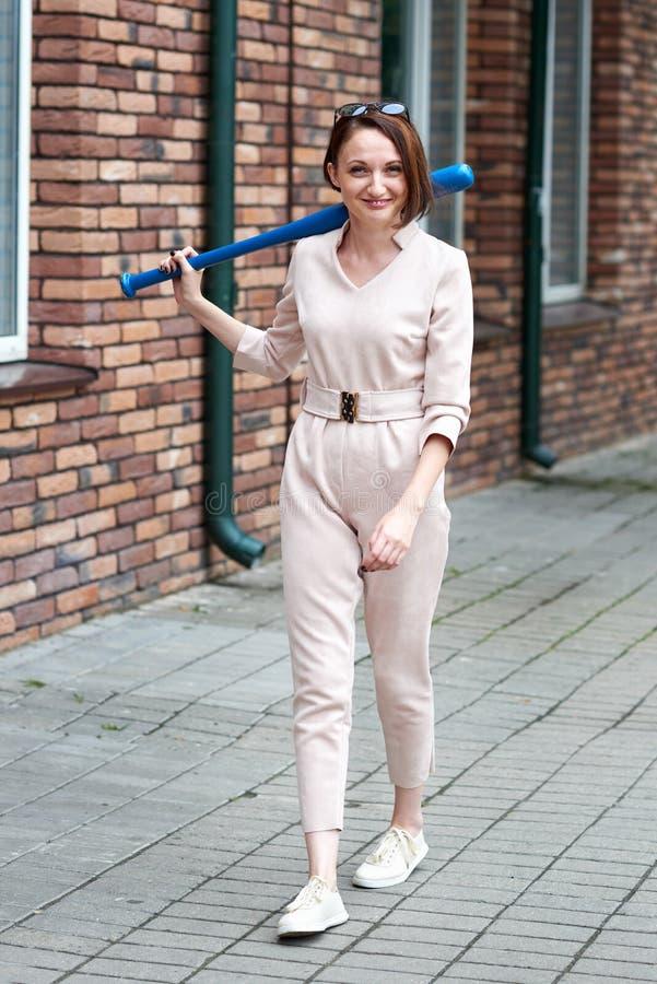 La ragazza che cammina giù la via ed ha una mazza da baseball fotografia stock libera da diritti