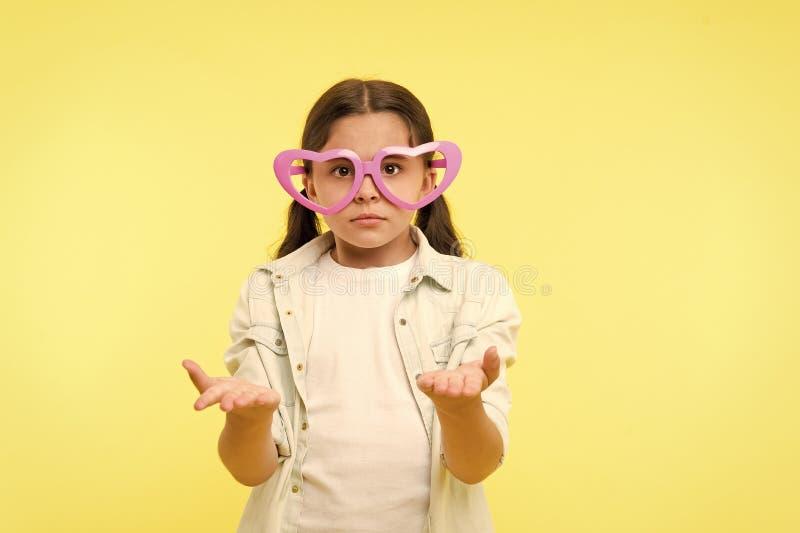 La ragazza che del bambino il cuore ha modellato gli occhiali sembra deludente La ragazza indossa il fronte deludente degli occhi immagini stock