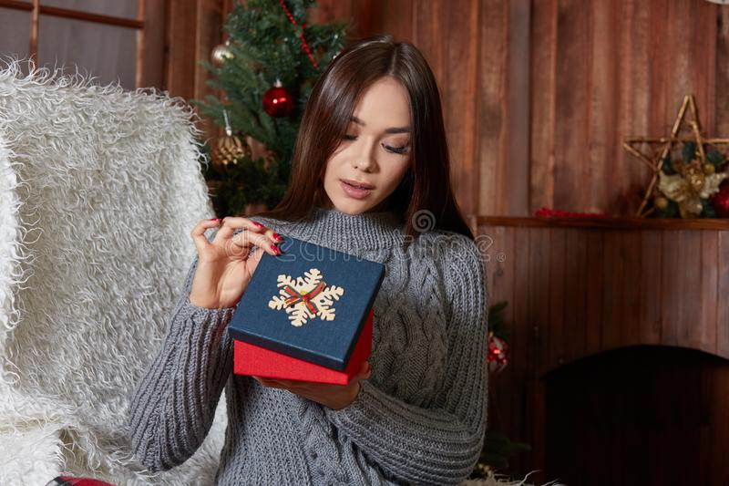La ragazza che disimballa il regalo di Natale sorpreso e contentissimo immagini stock libere da diritti