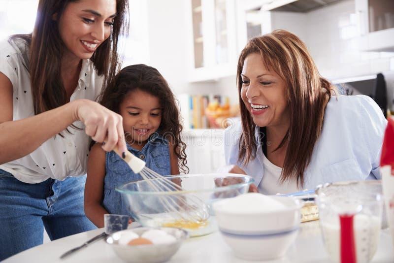 La ragazza che fa un dolce nella cucina con la sue mummia e nonna, si chiude su immagine stock