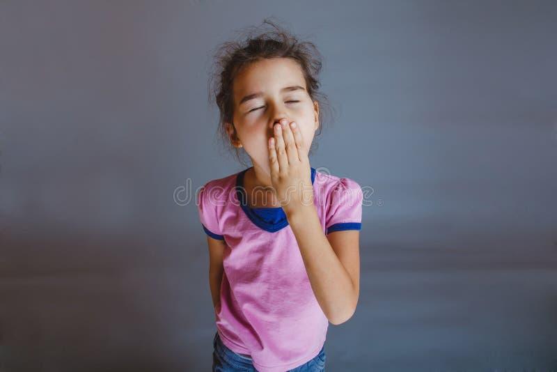La ragazza che il bambino è stanco chiude i suoi sbadigli della bocca sopra immagine stock