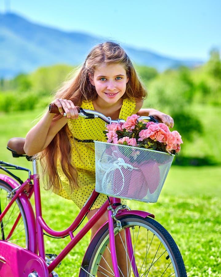La ragazza che indossa i pois rossi veste i giri va in bicicletta nel parco fotografia stock