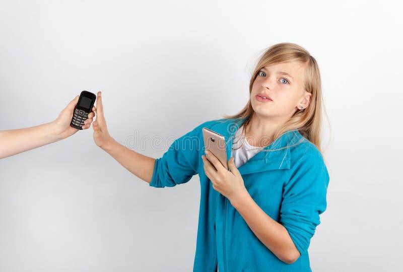 La ragazza che per mezzo dello smartphone rifiuta una mano che offre un cellulare semplice immagine stock