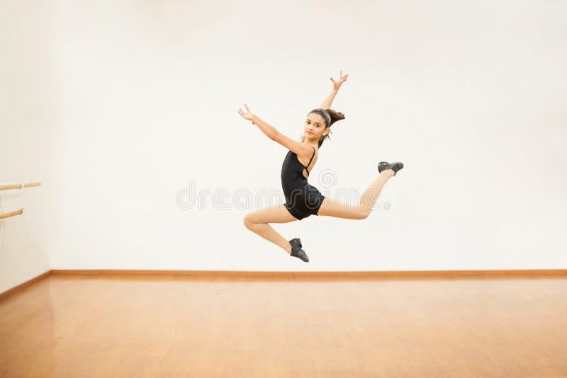 La ragazza che pratica alcuno salta nella classe di ballo fotografia stock libera da diritti