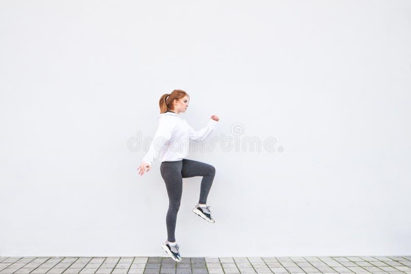La ragazza che salta contro lo sfondo di una parete bianca, scaldandosi prima del pareggiare e della supplica gli sport fotografia stock libera da diritti