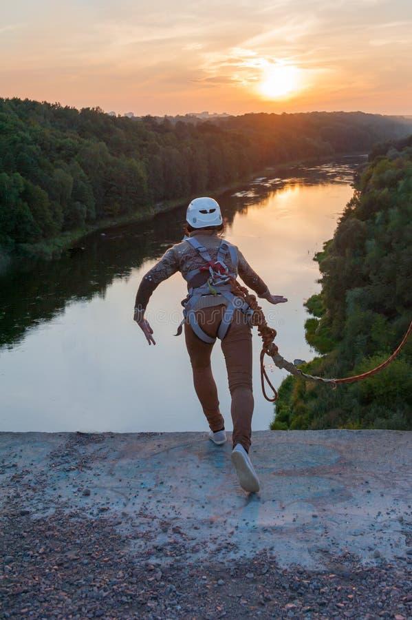 La ragazza che salta dal ponte Una ragazza con un tempo incredibile ? impegnata nello stile libero in bungee jumping Una ragazza  immagini stock