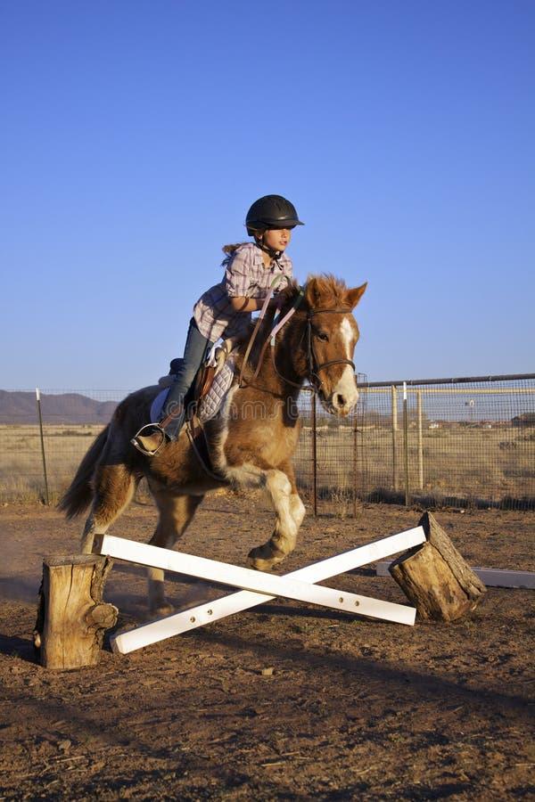 La ragazza che salta il suo cavallino fotografie stock