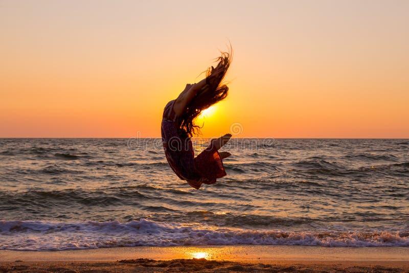 La ragazza che salta sulla costa di mare all'alba fotografia stock libera da diritti