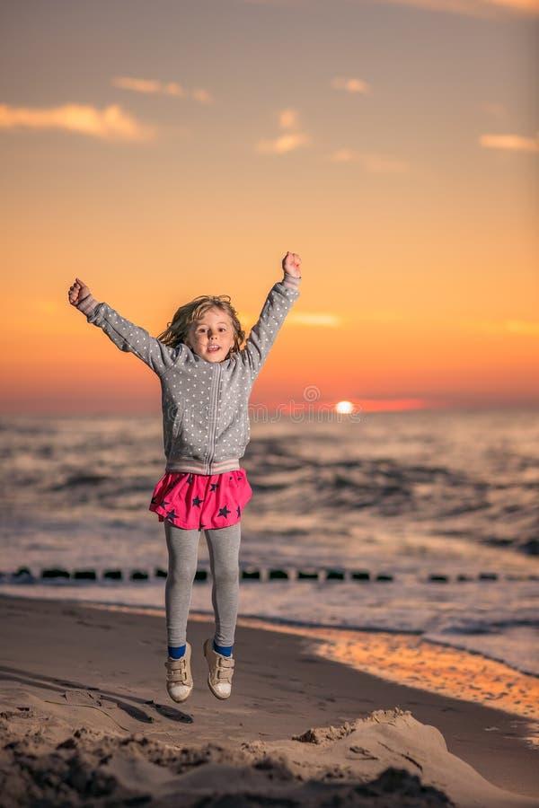 La ragazza che salta sulla spiaggia al tramonto fotografia stock libera da diritti