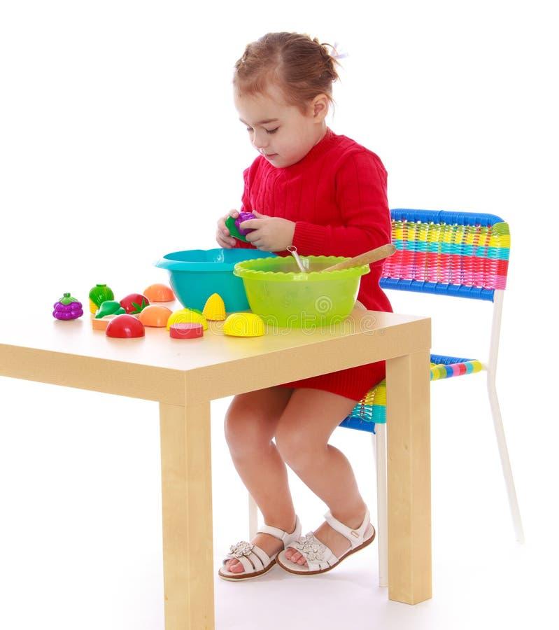 La ragazza che si siede alla tavola ed ai giochi artificiali fotografia stock libera da diritti