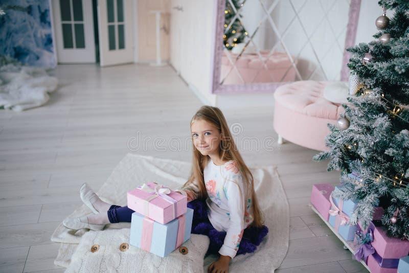 La ragazza che si siede con i contenitori di regalo si avvicina all'albero di Natale a casa fotografia stock libera da diritti