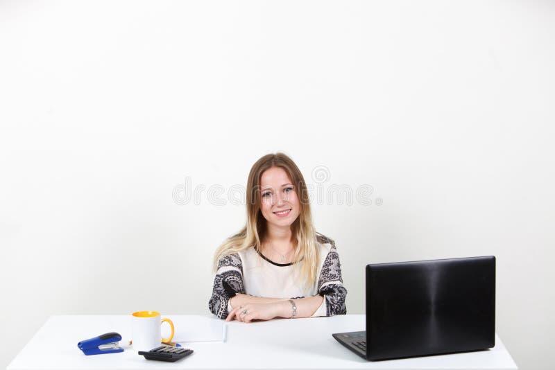 La ragazza che si siede dietro uno scrittorio nell'ufficio Un fondo bianco su fotografia stock libera da diritti