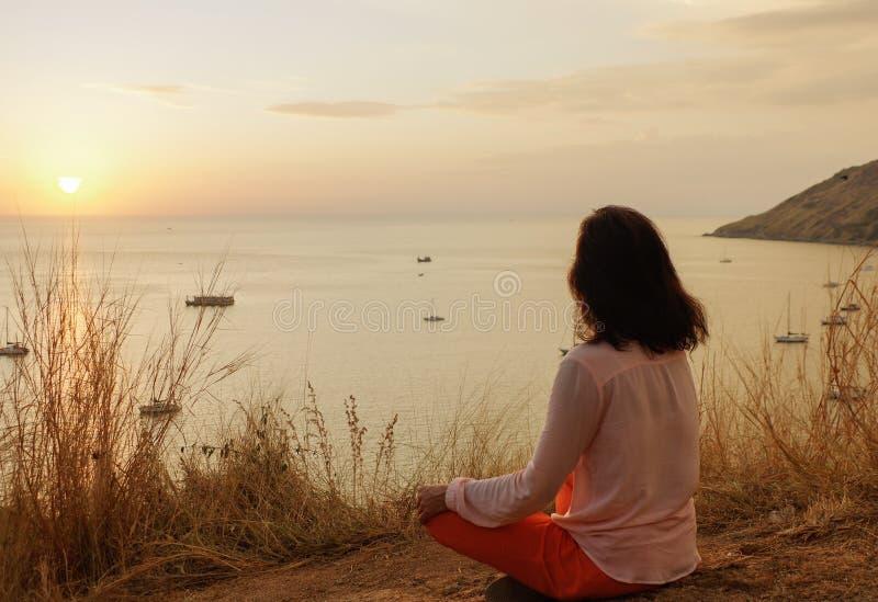 La ragazza che si siede nella posizione di meditazione del loto di yoga nella parte anteriore alla spiaggia sulle rocce una sorve immagini stock libere da diritti